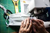 High Angle View Close-up of Mature Woman Sewing Protective Face Masks During Coronavirus Pandemic.