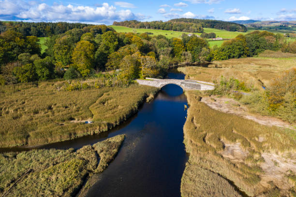High angle view from a drone of an old stone bridge crossing a river in Dumfries and Galloway south west Scotland The view from a drone of an old stone bridge crossing a small river that flows into an estuary in Dumfries and Galloway, south west Scotland. johnfscott stock pictures, royalty-free photos & images
