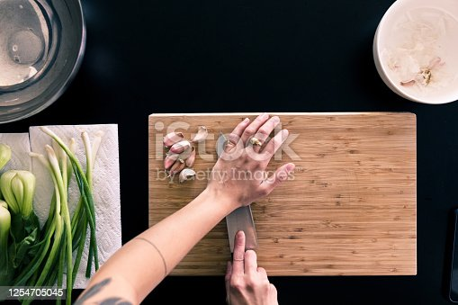 An unrecognizable woman crushes garlic with the flat side of a large knife for a recipe that includes leeks and green onions.