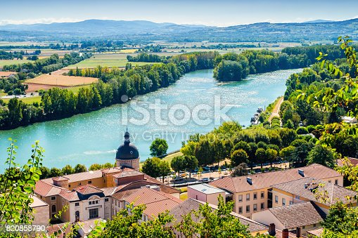 High angle view of trees, fileds, house roof, Saone river and Beaujolais hills in background of Trevoux beautiful town landscape in summer season with a bright sunlight. This pretty medieval town is located in Ain, Auvergne-Rhone-Alpes region in France near Lyon city along Saone river.