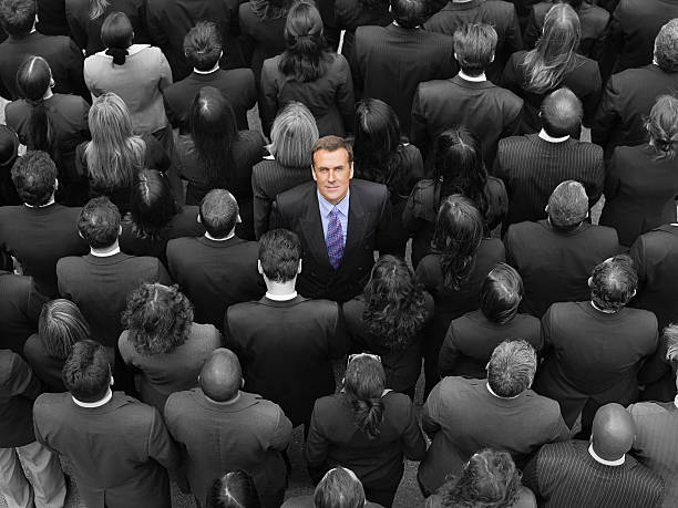 High angle view of a businessman standing amidst businesspeople High angle view of a businessman standing amidst businesspeople amidst stock pictures, royalty-free photos & images