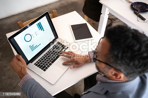 High angle view of a businessman using laptop in a restaurant