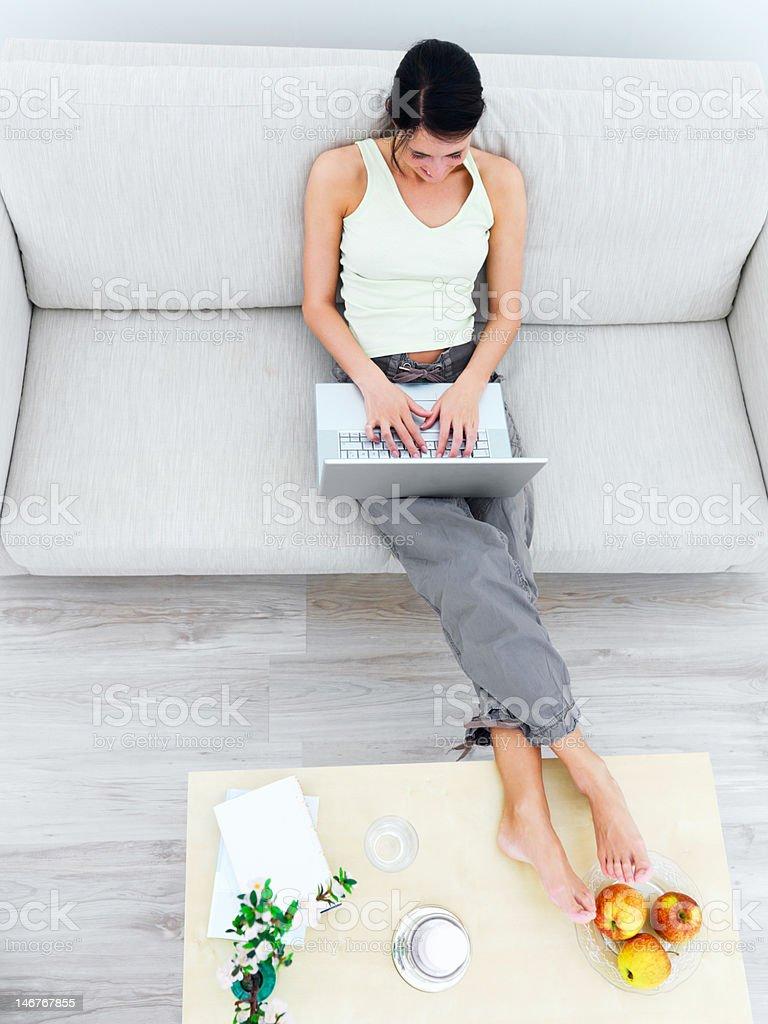 Верхний ракурс a Деловая женщина, используя ноутбук на диване стоковое фото
