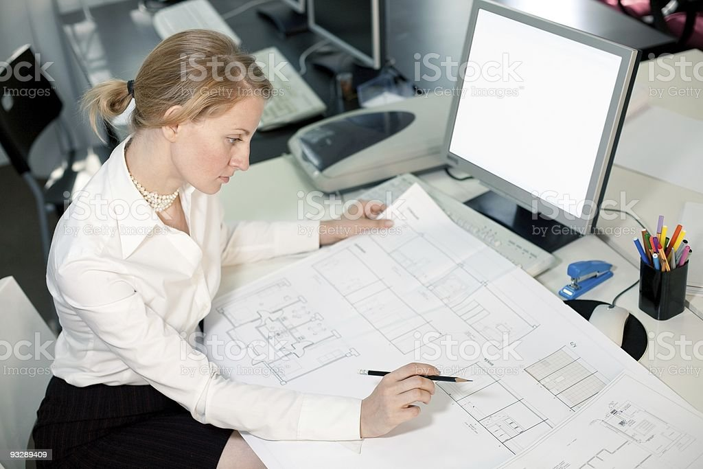 High angle view of a businesswoman working on blueprints royalty-free stock photo