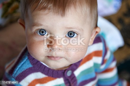 Close-up of a baby girl with stares at camera with curiousity, snot running from nose