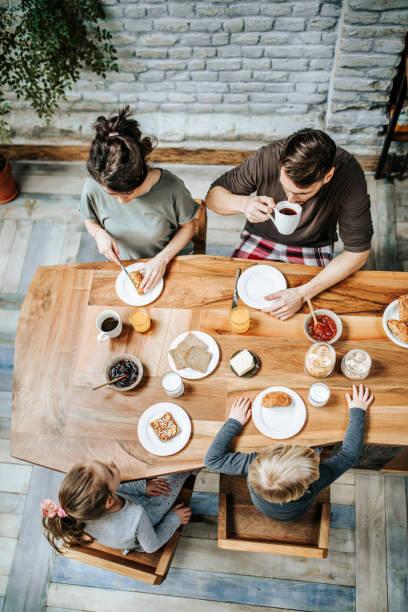 erhöhte ansicht einer familie, die ihr frühstück gemeinsam am esstisch essen. - küche aus paletten stock-fotos und bilder