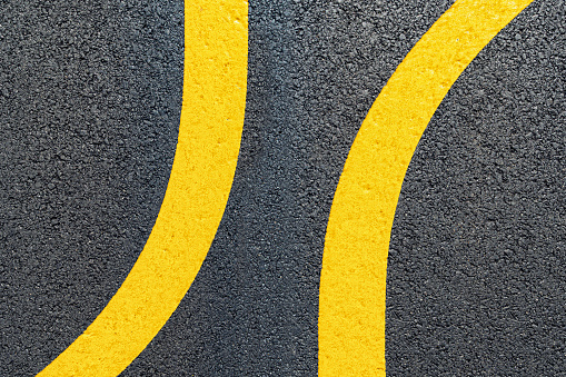 Directly above a freshly painted double yellow lane markers on a newly paved asphalt road that went astray.