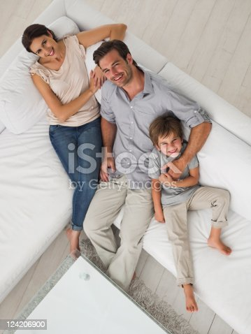 istock High angle view of a happy couple with child sitting on sofa 124206900