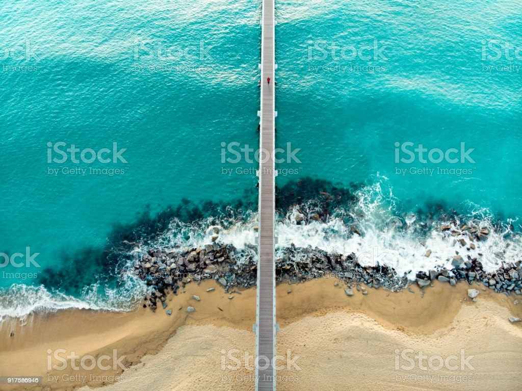 High angle view of a man running on wooden pier on beach stock photo