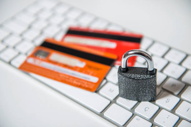 High angle view of a padlock with credit/debit cards over computer keyboard stock photo