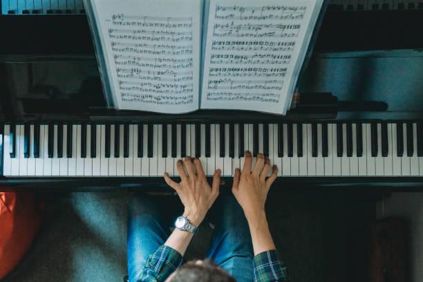 vue d'angle élevé d'un pianiste jouant du piano - piano photos et images de collection