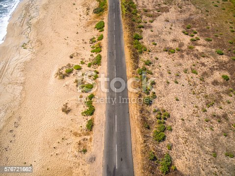 Aerial view of road near the sea. Sand and bushes on both sides of the road.