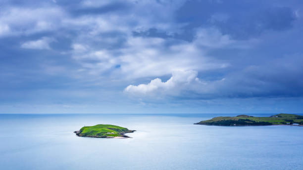 High angle view of a small island just off the coastline in a stretch of sea in south west Scotland The view from a drone across a stretch of sea called Auchencairn Bay with an island just off the coastline. The location is in Dumfries and Galloway, south west Scotland. johnfscott stock pictures, royalty-free photos & images