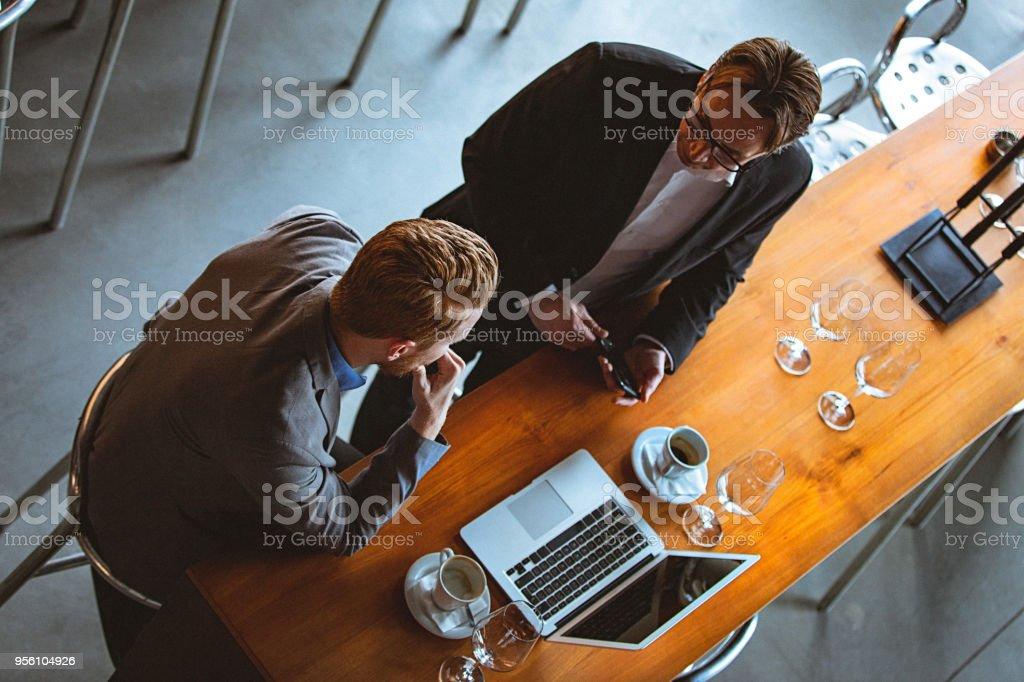 Alto ángulo visión de dos hombres teniendo una conversación en un Coffee Break en un Cafe / restaurante - foto de stock