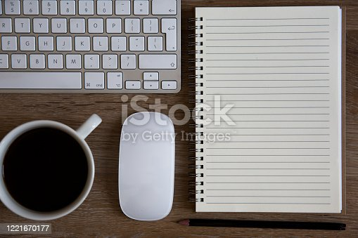 862672018 istock photo A high angle view of a vintage desktop or home office with coffee cup, keyboard, mouse and spiral notebook with a blank page for notes and copy space 1221670177
