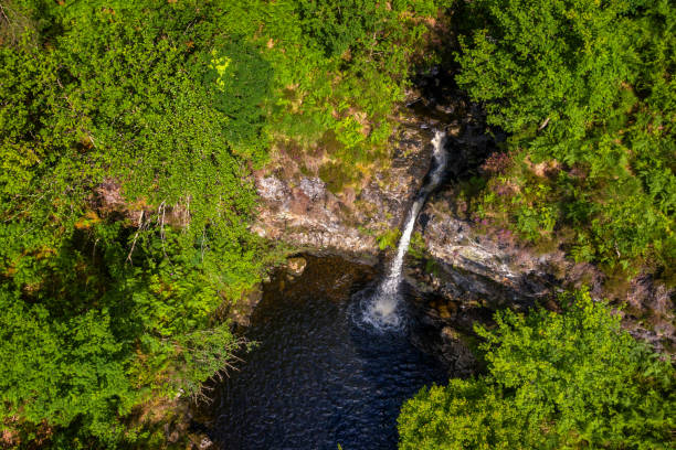 High angle view of a waterfall in an area of woodland in remote rural Dumfries and Galloway, south west Scotland A high angle view captured by a drone flying above a waterfall  in a forest in Scotland. The forest is in a remote rural area of Dumfries and Galloway in the south west of Scotland. During the summer the waterfall is hidden from a nearby footpath by the leaves on the surrounding trees. johnfscott stock pictures, royalty-free photos & images