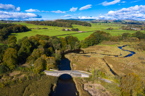High angle view of an old stone bridge in a rural area of Dumfries and Galloway south west Scotland The view from a drone of an old stone bridge crossing a small river that flows into an estuary in Dumfries and Galloway, south west Scotland. johnfscott stock pictures, royalty-free photos & images