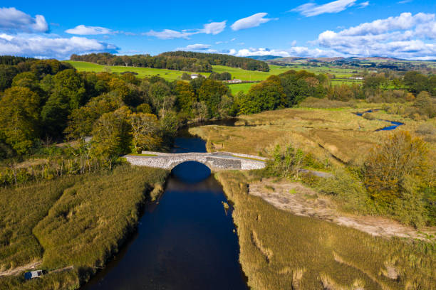 High angle view of an old stone bridge in Dumfries and Galloway south west Scotland The view from a drone of an old stone bridge crossing a small river that flows into an estuary in Dumfries and Galloway, south west Scotland. johnfscott stock pictures, royalty-free photos & images