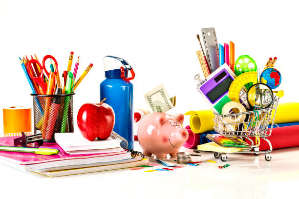 High angle view of back to school office supplies on white background with piggy bank and dollar banknote stock photo