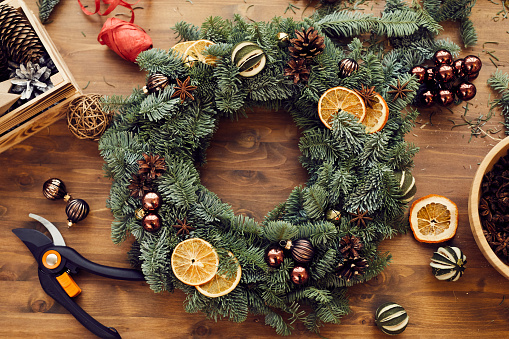 High angle view of beautiful holiday wreath decorated orange slices, fir tree cones and small balls placed on wooden table among decorations and tools