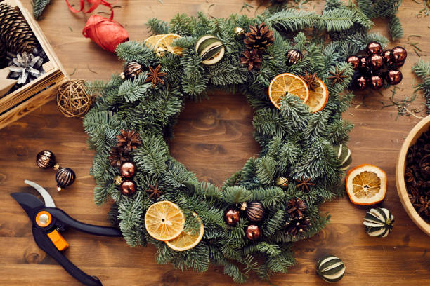 High angle view of beautiful holiday wreath decorated orange slices, fir tree cones and small balls placed on wooden table among decorations and tools stock photo