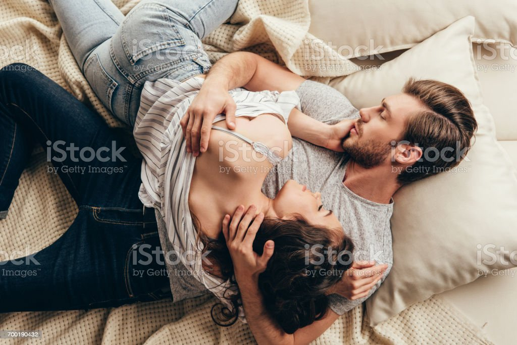 High angle view of beautiful young couple in love hugging while lying on bed High angle view of beautiful young couple in love hugging while lying on bed Adult Stock Photo