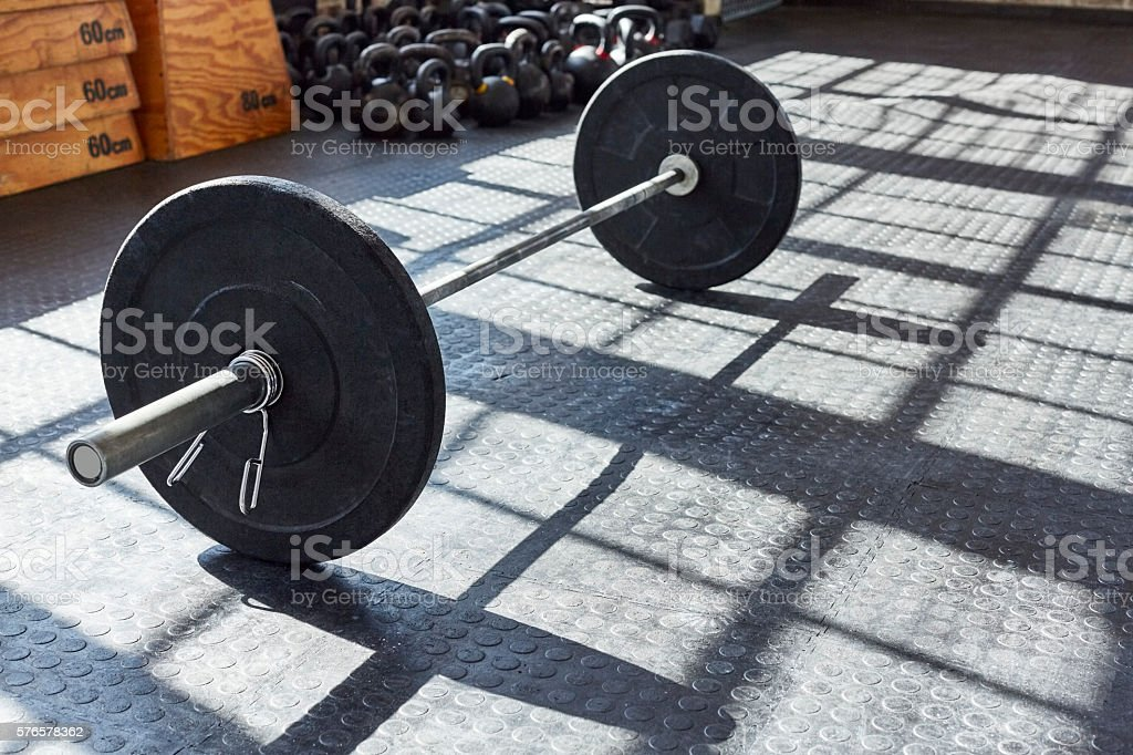High angle view of black barbell on floor in gym stock photo