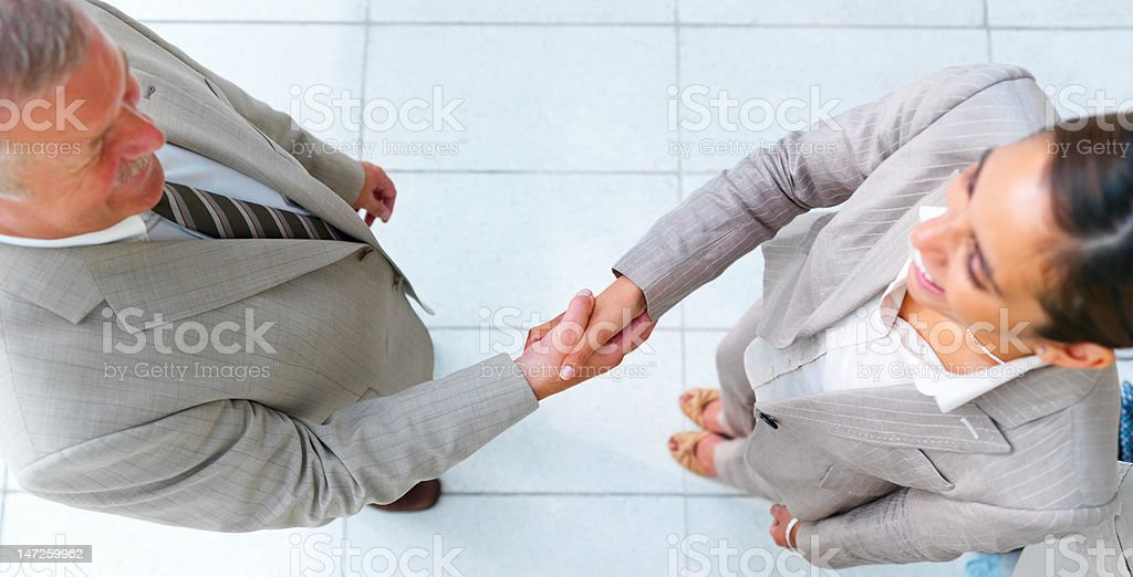 High angle view of business colleagues shaking hands royalty-free stock photo