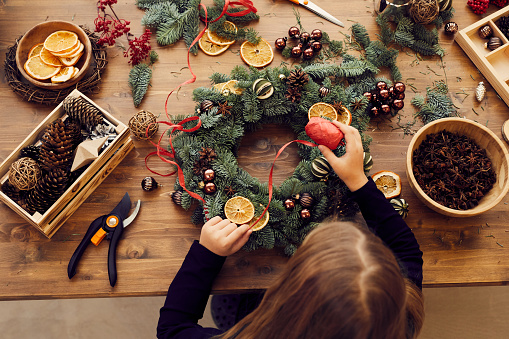 High angle view of busy woman standing at desk and using decorative ribbon while making Christmas wreath
