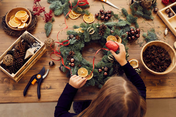 High angle view of busy woman standing at desk and using decorative ribbon while making Christmas wreath DIY Christmas wreath decorating stock pictures, royalty-free photos & images