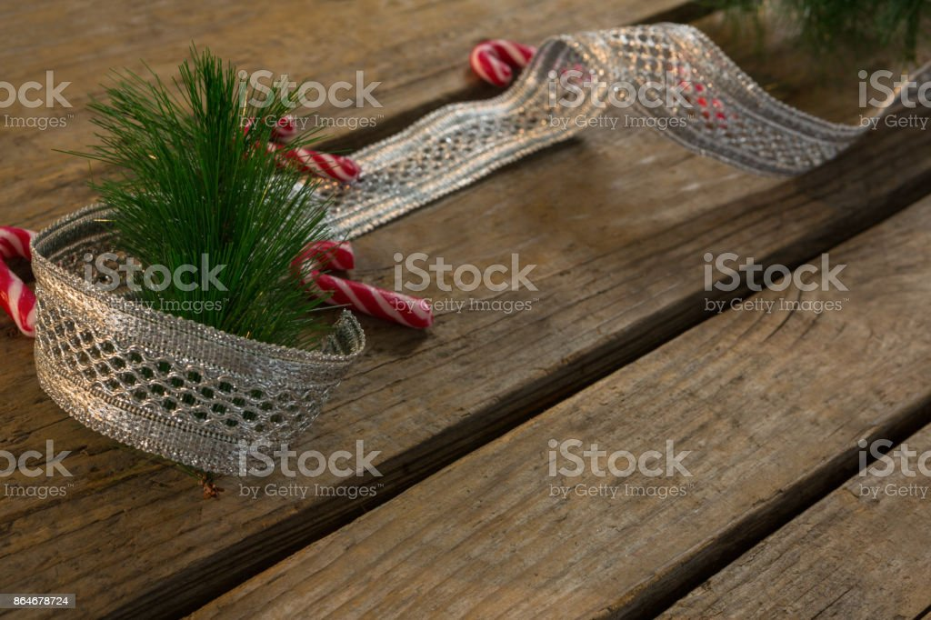 High angle view of candy canes with ribbon and pine needles on table stock photo