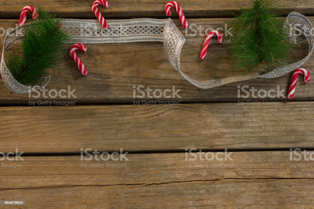 High angle view of candy canes with twigs and ribbon on table stock photo