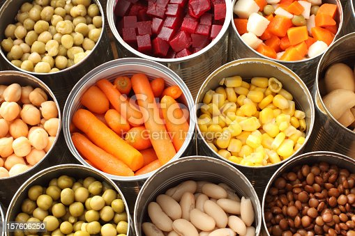 Twelve cans of open vegetables sit next to one another in three rows.  There are peas, carrots, beats, snow peas, corn, chick peas and Lima beans in the cans.