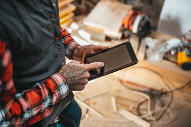 erhöhte ansicht der tischler mit tablette während der arbeit an möbel-projekt - tattoo maker online stock-fotos und bilder