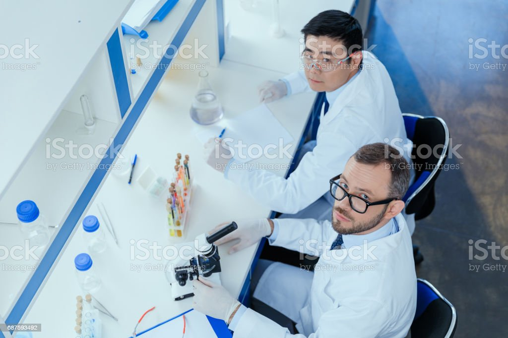 High angle view of chemists in eyeglasses and lab coats working together in chemical laboratory stock photo