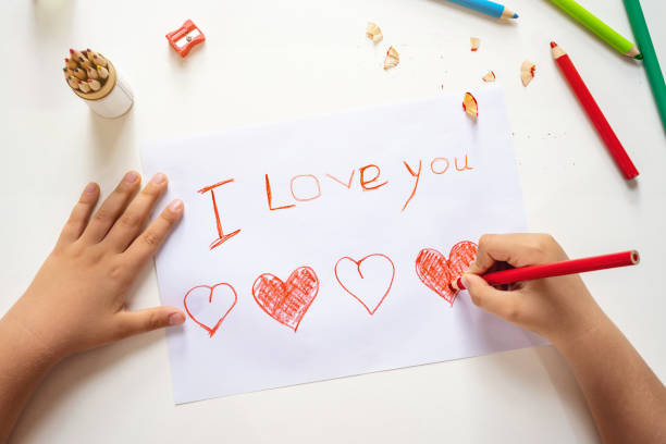 High angle view of child drawing I love you sign stock photo