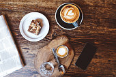Vintage low key image of a coffee on the table in a cafe in East London. Overhead high angle view on a cappuccino and some sweets, a delicious chocolate cake.