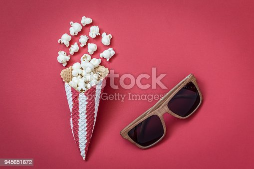 956942702 istock photo High angle view of cone with popcorn and movie theater eyeglasses on red background minimalistic concept. 945651672