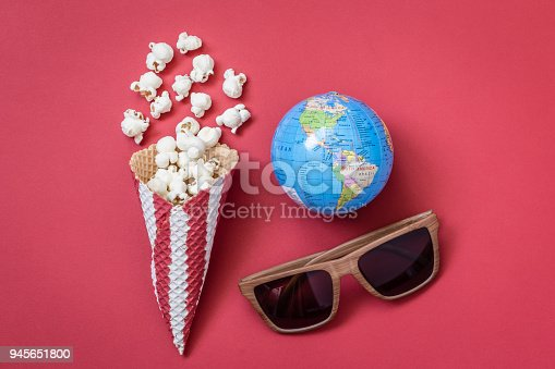 956942702 istock photo High angle view of cone with popcorn and movie theater eyeglasses with globe model on red background minimalistic concept. 945651800