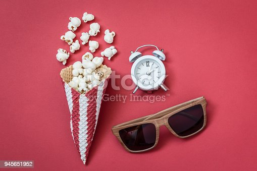 956942702 istock photo High angle view of cone with popcorn and movie theater eyeglasses with small alarm clock on red background minimalistic concept. 945651952