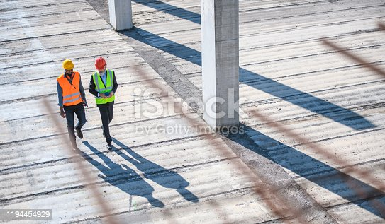 Elevated view through defocused rebar in foreground of construction site foreman and manager walking and talking.