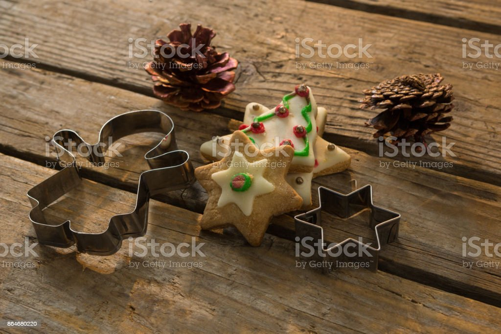 High angle view of cookies with pine cones and pastry cutters on table stock photo
