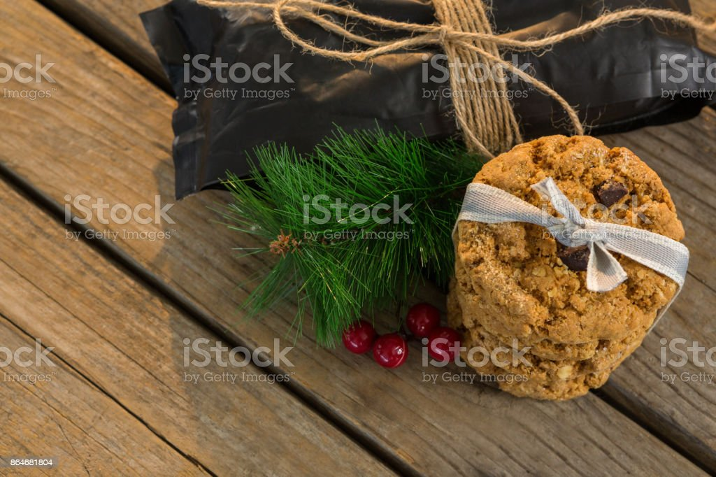 High angle view of cookies with pine needles and cheeries by plastic bag on table stock photo