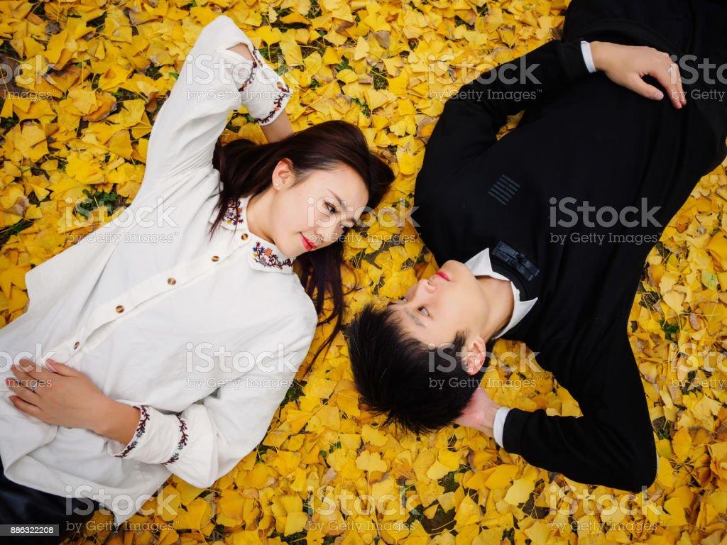 秋の地面に横たわっている若い中国人のカップルのハイアングルは黄金のイチョウ葉、愛、恋人概念の完全で覆われています。 - 2人のロイヤリティフリーストックフォト