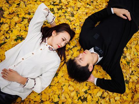 秋の地面に横たわっている若い中国人のカップルのハイアングルは黄金のイチョウ葉愛恋人概念の完全で覆われています - 2人のストックフォトや画像を多数ご用意