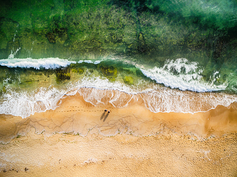 istock High angle view of couple standing on the beach 988351198