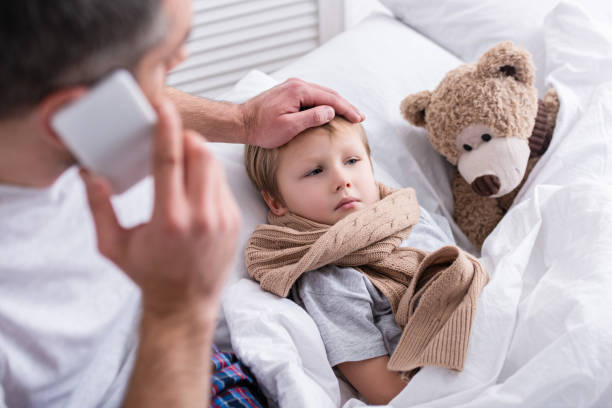 high angle view of daddy talking by smartphone and touching sick son forehead in bedroom - condizione medica foto e immagini stock