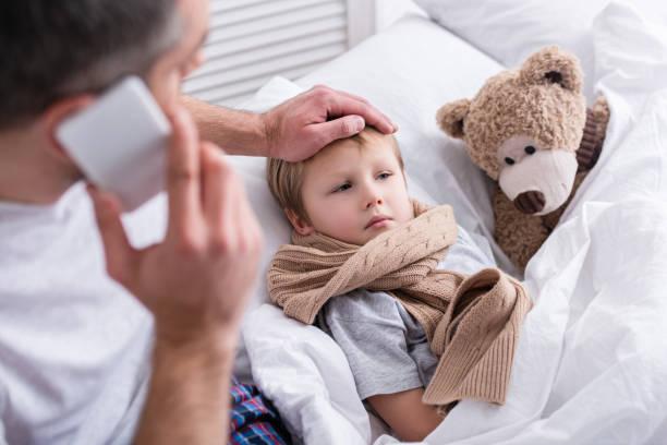 vista de ángulo alto de papá hablando por teléfono inteligente y tocar la frente del hijo enfermo en dormitorio - enfermedad fotografías e imágenes de stock
