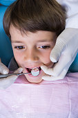 High angle view of dentist holding equipment while examining boy at medical clinic