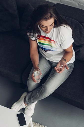 istock high angle view of depressed young transgender man with pills and glass of water sitting on couch 1061259458